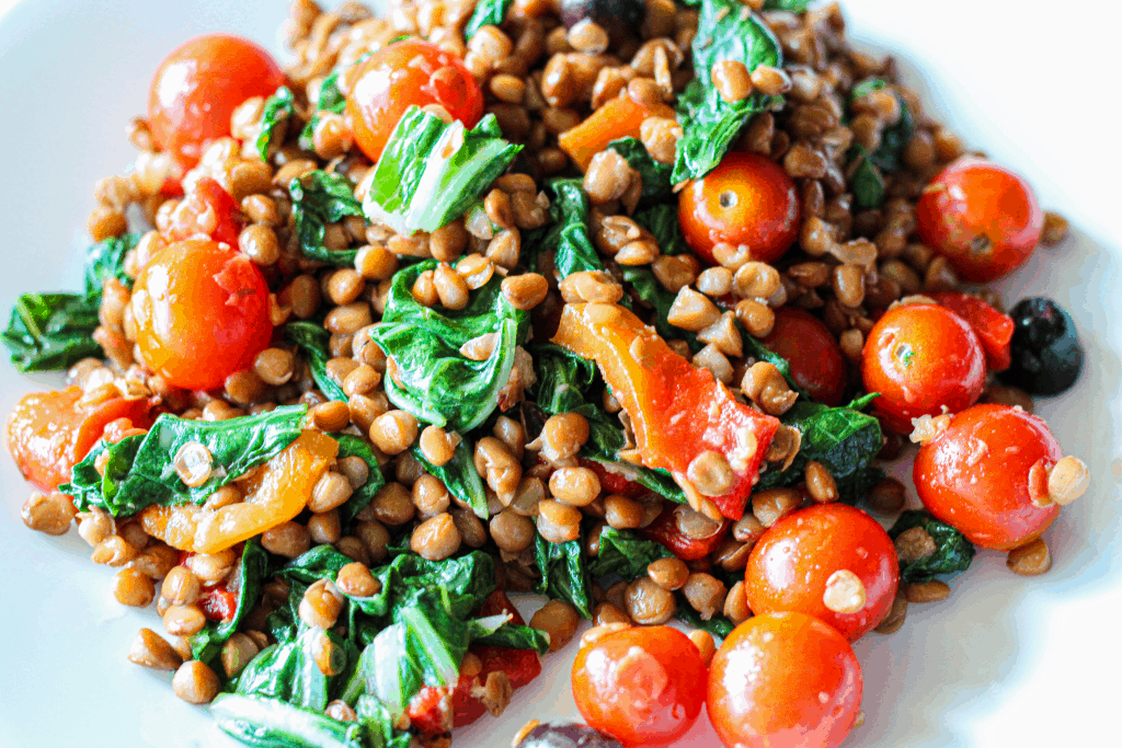 Lentil salad with ginger dressing, cherry tomatoes, kale and olives.